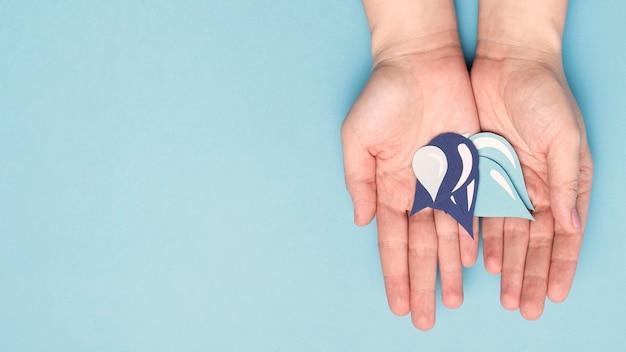 Vista superiore delle mani che tengono le gocce di acqua di carta con lo spazio della copia Foto Premium