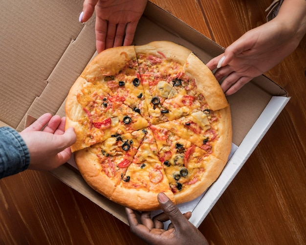 Mani di vista dall'alto che prendono le fette di pizza Foto Premium