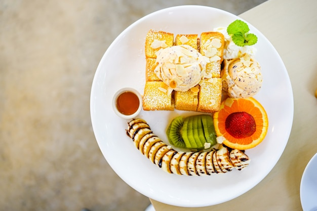 Vista dall'alto di pane tostato al miele servito con frutta mista, banana a fette, gelato e condita con fetta di mandorle e sciroppo di miele nel piatto bianco. Foto Premium
