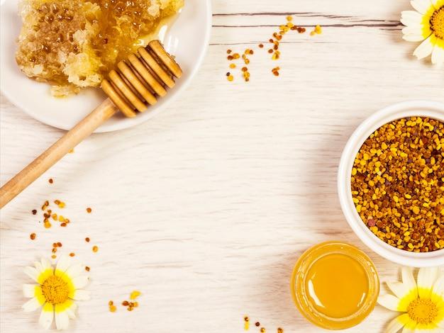 Vista dall'alto del nido d'ape; miele e polline d'api con fiore giallo bianco Foto Premium