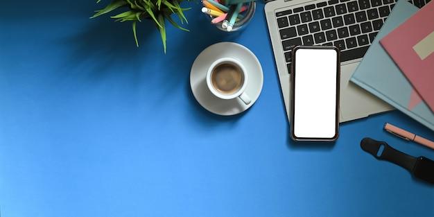 Immagine di vista superiore dello smartphone bianco dello schermo in bianco che mette sullo scrittorio funzionante variopinto che circondato dalle penne dell'indicatore, dai taccuini, dallo smartwatch, dalla tazza di caffè, dal supporto della matita e dalla pianta in vaso. area di lavoro ingombra. Foto Premium