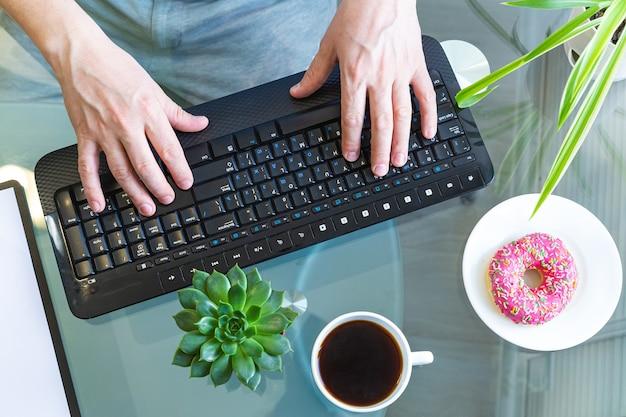Vista dall'alto delle mani maschile sulla tastiera di un computer. Foto Premium