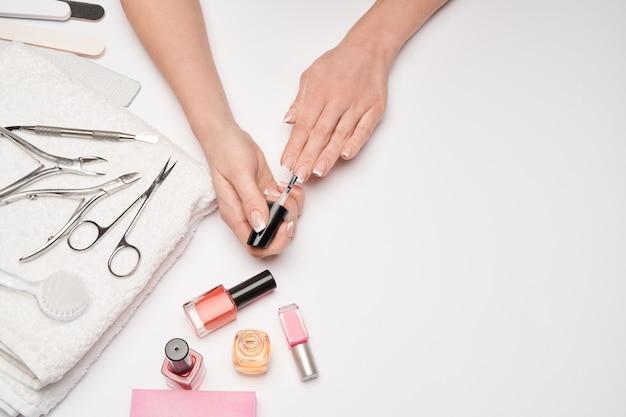 Vista dall'alto del set di strumenti per manicure per la cura delle unghie su una superficie chiara: pennello, forbici, smalto per unghie, lima e pinzette Foto Premium