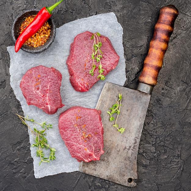 Vista dall'alto di carne su mannaia con spezie e peperoncino Foto Premium