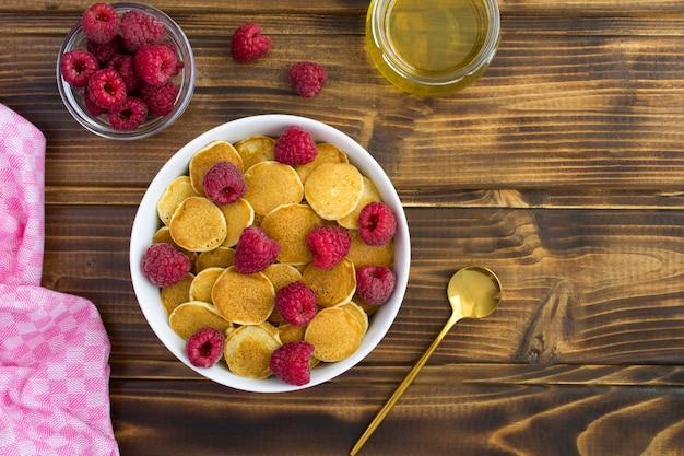 Vista dall'alto di mini frittelle con lamponi nella ciotola bianca sul tavolo di legno Foto Premium