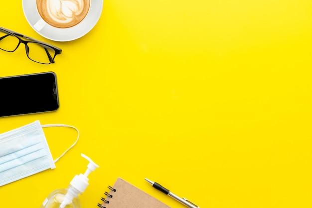Vista dall'alto nuova maschera preventiva, occhiali da vista, smartphone, gel igienizzante per le mani, tazza di caffè e libro. malattia da coronavirus (covid-19) o concetto sano Foto Premium