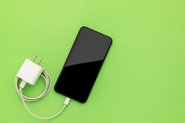 Vista dall'alto nuovo smartphone con caricatore bianco Foto Premium