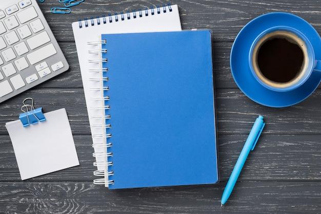 Vista superiore dei taccuini sullo scrittorio e sulla tazza di caffè di legno Foto Premium