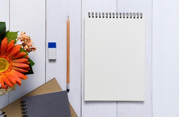 Vista superiore del taccuino in bianco a spirale aperta con la matita sul fondo di legno dello scrittorio Foto Premium