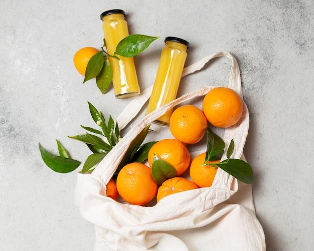 Vista dall'alto arance in borsa di tote con bottiglie di succo Foto Premium