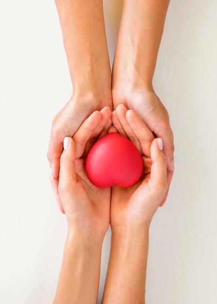Vista dall'alto del paio di mani che tengono a forma di cuore con cura Foto Premium