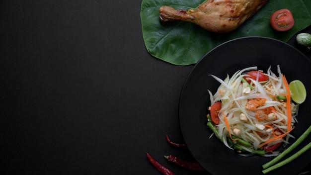 Vista superiore dell'insalata di papaia sulla banda nera, griglia del pollo sul taro verde a Foto Premium