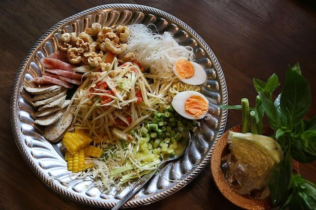 Vista dall'alto insalata di papaya o som tum in cibi thailandesi con carne di maiale acida, uovo sodo. Foto Premium