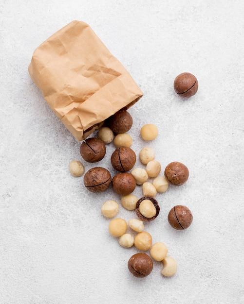 Sacchetto di carta con vista dall'alto riempito con noci di macadamia e cioccolato Foto Premium