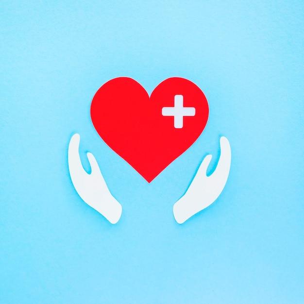 Vista dall'alto del cuore di carta e delle mani per il giorno del cuore Foto Premium