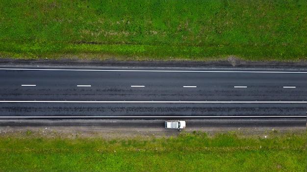 Vista dall'alto. parte dell'autostrada in primavera. lungo i prati verdi. su un tratto di strada è parcheggiata un'auto Foto Premium