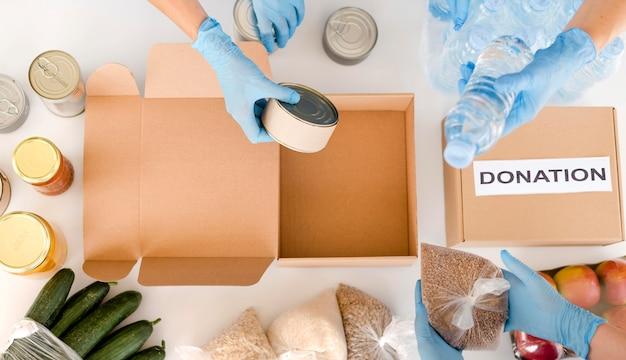 Vista dall'alto di persone che preparano scatola con donazione di cibo Foto Premium