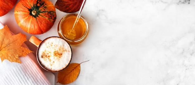 Vista dall'alto di latte speziato di zucca o caffè con schiuma cremosa, piccola zucca arancione, maglione bianco e foglie di autunno su sfondo di marmo bianco. banner lungo. copia spazio Foto Premium
