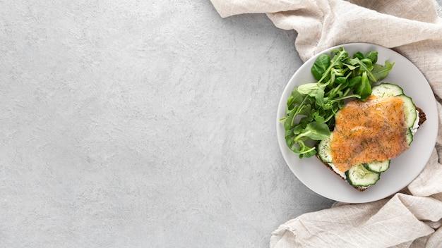 Vista dall'alto panino con cetrioli e salmone sul piatto con copia-spazio Foto Premium