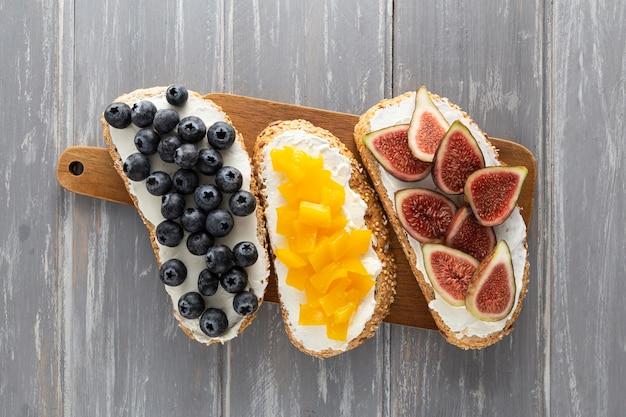 Vista dall'alto panini con crema di formaggio e frutta sul tagliere Foto Premium