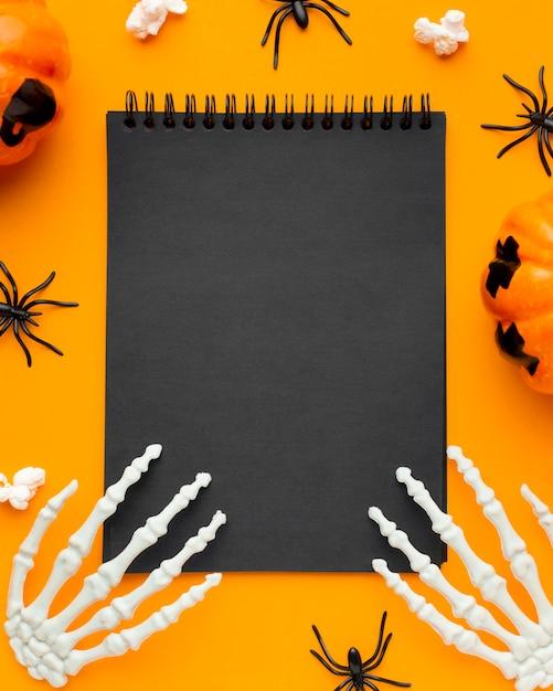 Mani di scheletro vista dall'alto sul blocco note per halloween Foto Premium