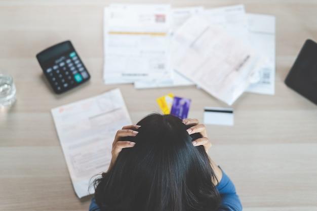 Punto di vista superiore della donna asiatica giovane sollecitata che prova a trovare soldi per pagare debito della carta di credito. messa a fuoco selettiva a portata di mano Foto Premium