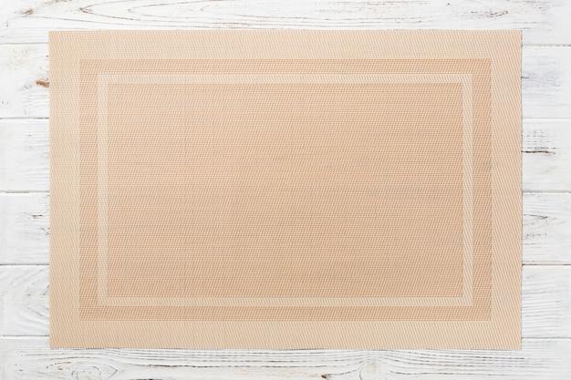 Vista superiore della stuoia marrone del tessuto per la cena su fondo di legno con lo spazio della copia Foto Premium