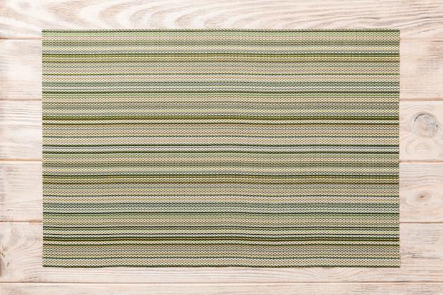 Vista superiore della stuoia verde del tessuto per la cena su fondo di legno con lo spazio della copia Foto Premium