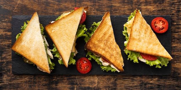 Vista dall'alto di sandwich di triangolo su ardesia con pomodori Foto Premium