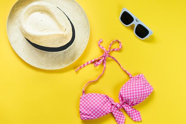 Vista dall'alto di due pezzi costume da bagno a scacchi rosa, occhiali da sole bianchi e cappello di paglia su giallo Foto Premium