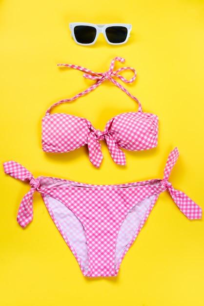 Vista dall'alto di due pezzi costume da bagno a scacchi rosa e occhiali da sole bianchi su giallo Foto Premium