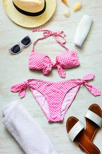 Vista dall'alto di due pezzi costume da bagno rosa e accessoties spiaggia su legno. Foto Premium