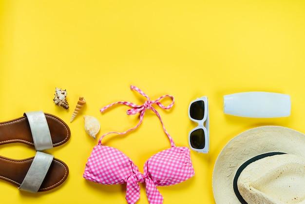 Vista dall'alto di due pezzi rosa costume da bagno e accessoties spiaggia su sfondo giallo. Foto Premium