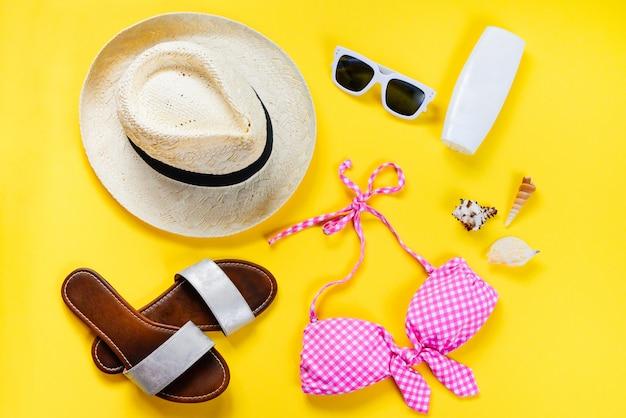 Vista dall'alto di due pezzi rosa costume da bagno e accessoties spiaggia su giallo Foto Premium