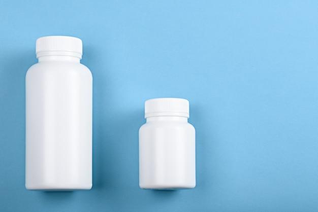 Vista dall'alto due bottiglie di plastica bianche su sfondo blu per il marchio Foto Premium