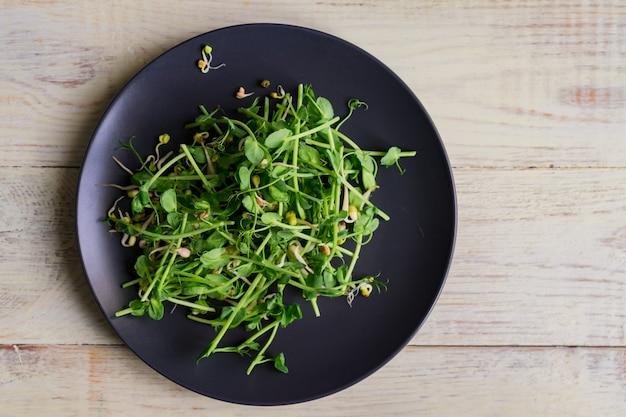 Vista superiore dell'insalata sana del vegano fatta dei germogli microgreen dei piselli e dei fagioli germogliati sulla parete di legno Foto Premium