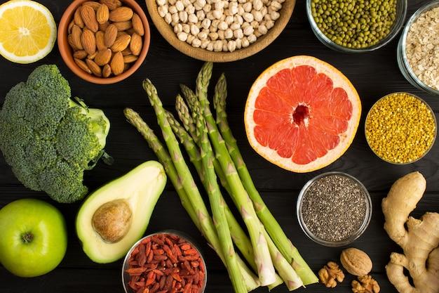 Vista dall'alto di verdure, frutta, legumi, noci e polline d'api Foto Premium