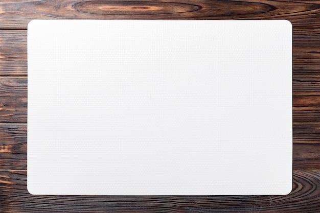 Vista dall'alto della tovaglietta bianca per un piatto. tavolo di legno Foto Premium