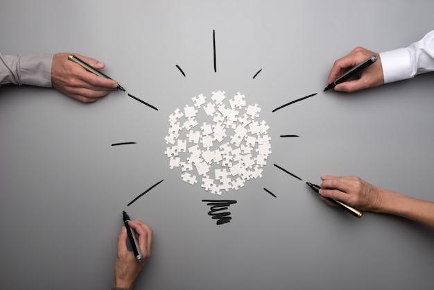 Vista dall'alto di pezzi di puzzle sparsi bianchi e mani di persone di affari Foto Premium