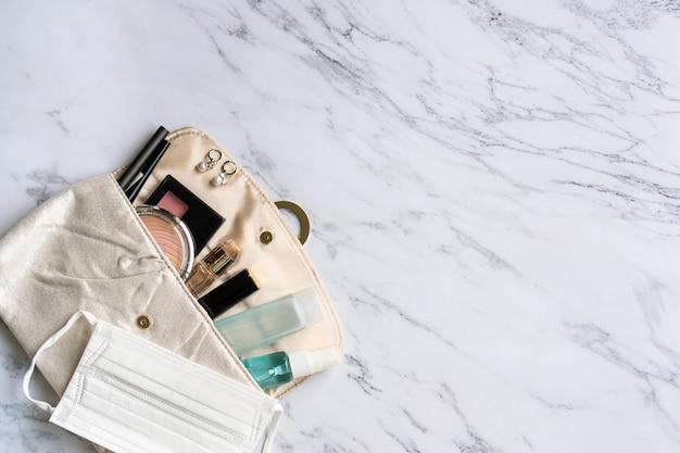 Vista superiore degli accessori della donna, del prodotto disinfettante, dello spruzzo di alcool e della maschera di protezione sul sacchetto, concetto di bellezza. copia spazio, disteso Foto Premium