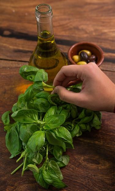 Vista superiore delle mani della donna che toccano foglie di basilico fresco con olio d'oliva e olive su un tavolo di legno Foto Premium