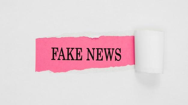 Strappato giornale di notizie false sul muro rosa e bianco Foto Premium