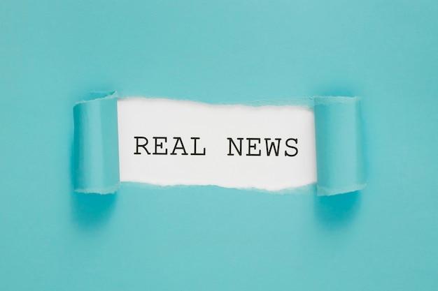 Strappato il giornale di notizie reali sul muro blu e bianco Foto Premium