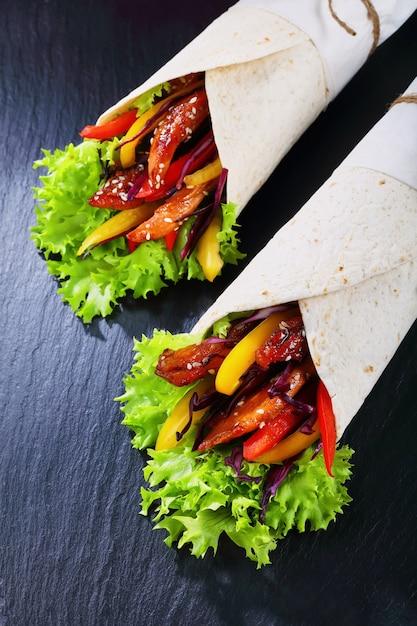 Tortilla arrotolata con insalata di cavolo rosso, strisce di peperoni e carne di pollo fritta Foto Premium