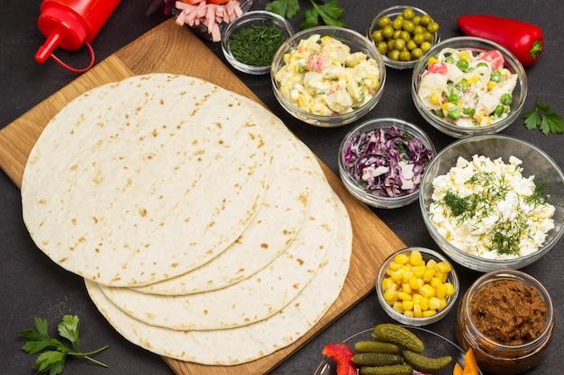 Impacchi di tortilla e ripieno di verdure per tortilla in ciotole di vetro. Foto Premium