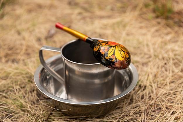 Una tazza turistica con un cucchiaio che si trova in un piatto sullo sfondo della natura. Foto Premium