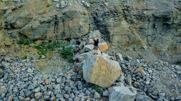 Un turista è in piedi su una grossa pietra con le mani in alto vicino alla roccia. Foto Premium