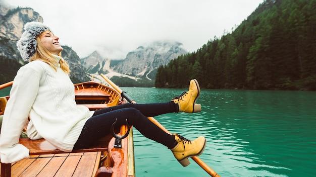 Donna turistica in barca a remi in legno tradizionale sul lago di braies alpino italiano Foto Premium