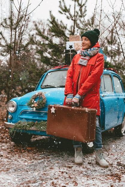 Verso l'avventura. giovane donna con una vecchia valigia sta aspettando un viaggio su una vecchia macchina sullo sfondo di una foresta invernale. tempo di vacanze di natale. Foto Premium