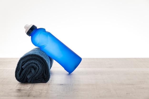 Asciugamano e bottiglia con acqua per allenamento in palestra Foto Premium